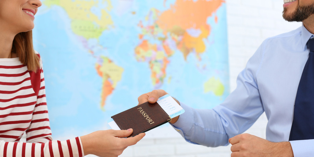 Male manager giving passport with ticket to client