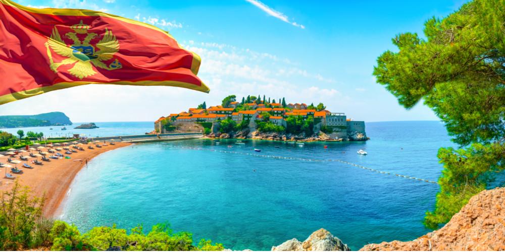 Flag and beach near the island of Sveti Stefan