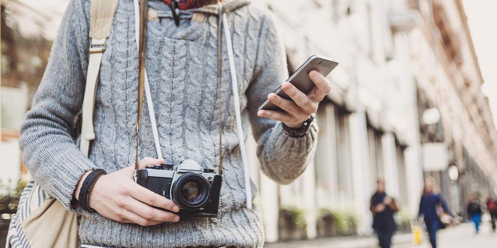 Traveler man using mobile phone on the street