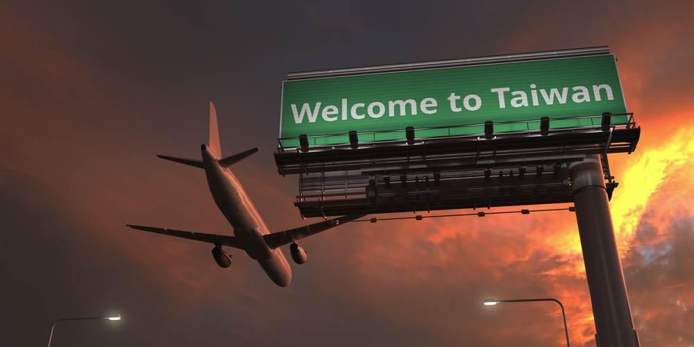 Airplane flies above welcome to taiwan highway sign
