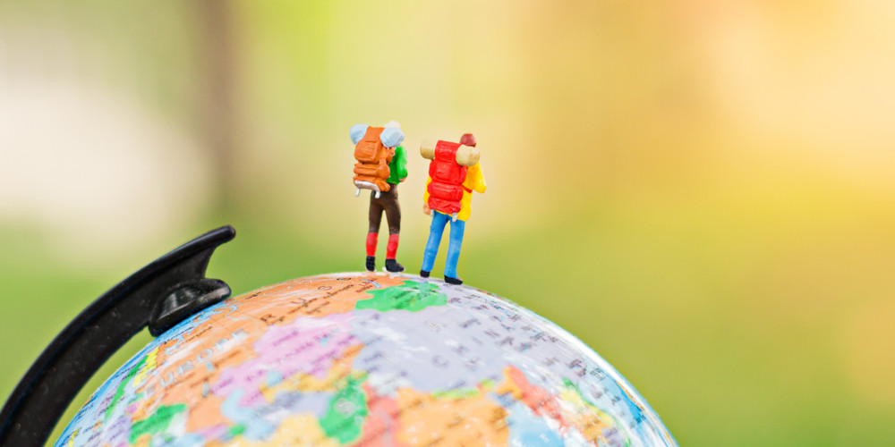 Travelers with backpack standing on world map