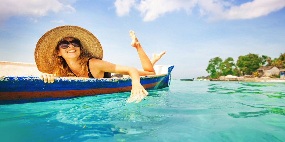 Tourist woman rowing a boat on paradise island