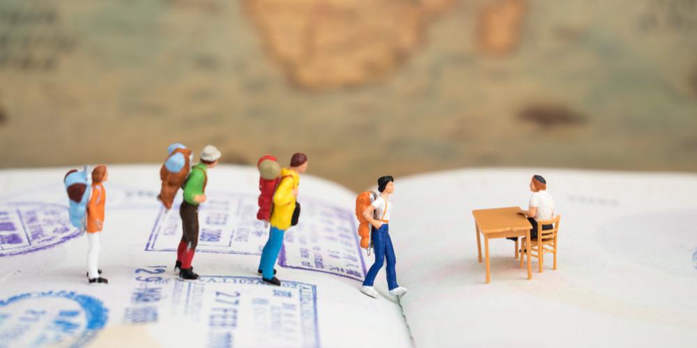 Miniature figure, younger traveler standing on visa stamp