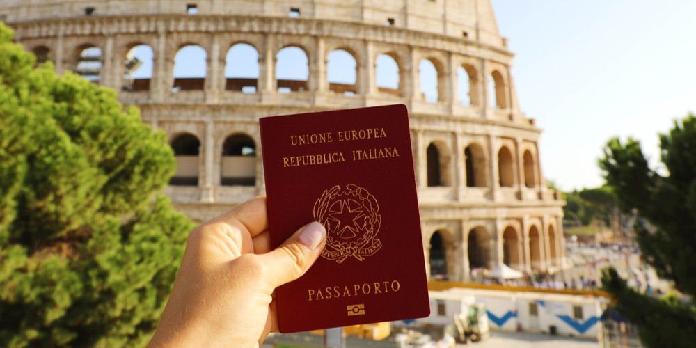 Holding Italian passport in front of Colosseum in Rome