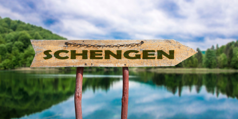 Schengen wooden arrow road sign against lake and forest background