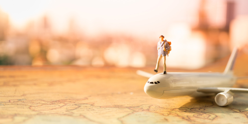 Miniature people on airplane using as background travel or business concept