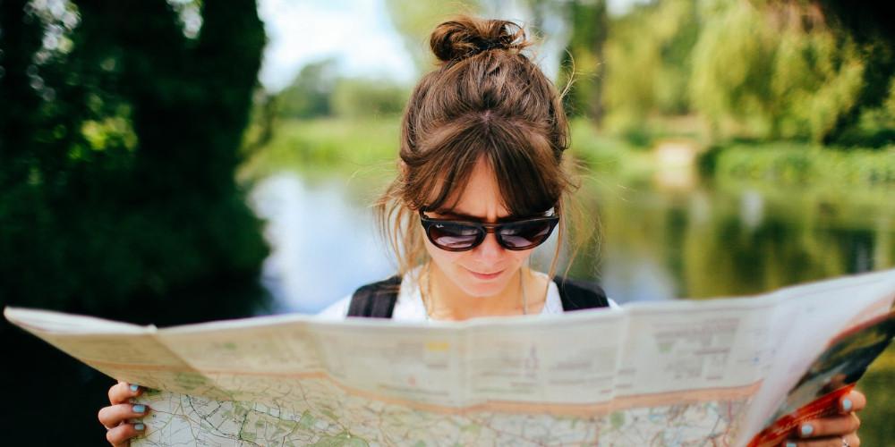 Tourist woman reading map