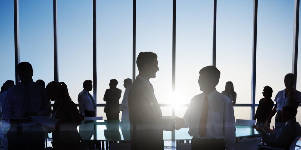 Global Investors Shaking Hands at Sunset