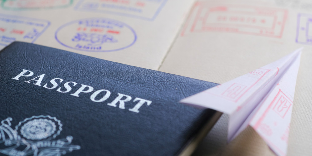 Folded paper airplane with entry stamps on the page of passport