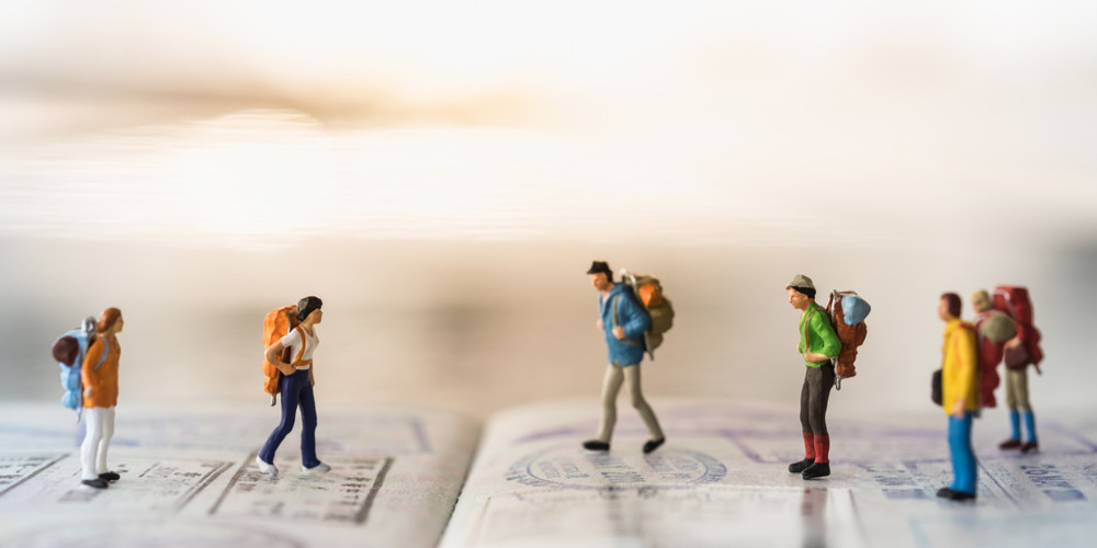 Group of miniature people figures walking backpack and standing on passport