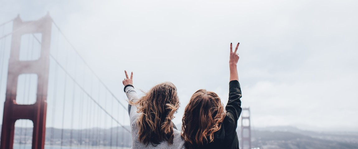girls enjoying with hands up in air