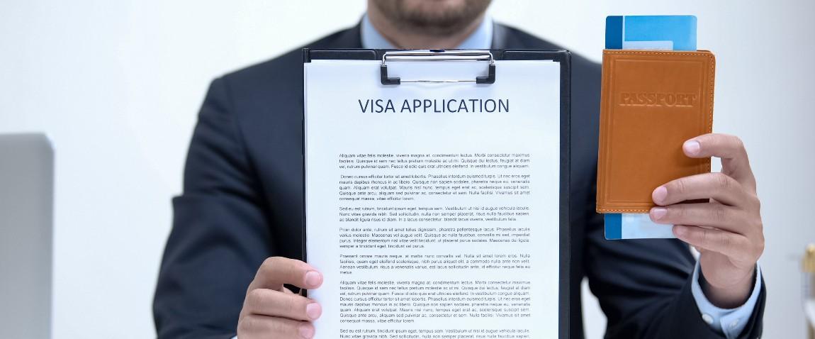 man holding visa application and passport