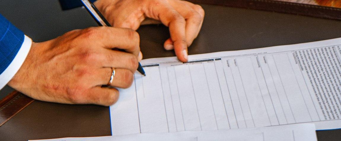 mujchina podpisivayushiy dokument