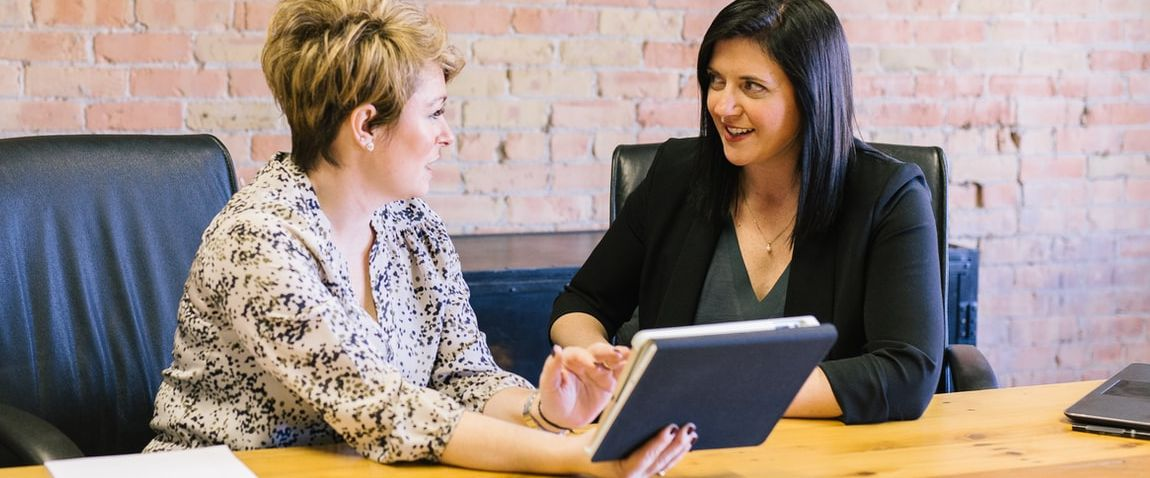 two women sitting consulting